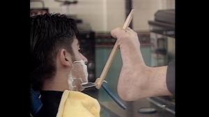 わざわざ足を使って髭を剃る理容師