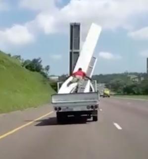 荷台の荷物に捕まって移動するも失敗した男