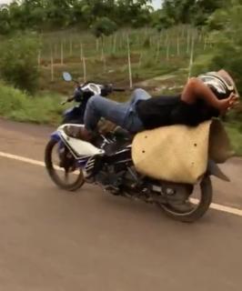 寝ながらバイクを運転する器用な男
