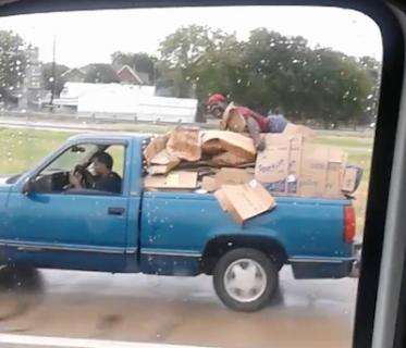 荷台の荷物にしがみついて移動する男