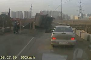 突然空いた穴で横転するトラック