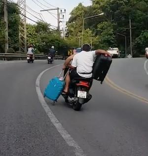 スーツケース2個を抱えてバイクに乗る男