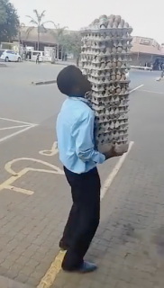 絶対無理だろうと思う数の卵を頭に乗せて運ぶ男