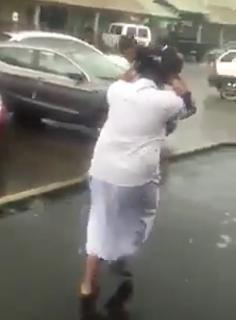 傘の代わりに子どもで雨をしのぐ父