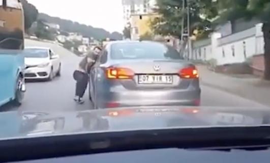 走行中の車にしがみつく男