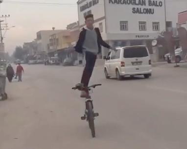 見事なバランスで自転車の上に立つ少年