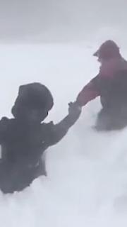 雪に覆われた道なき道を進む人々